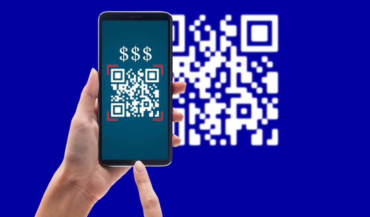 Na imagem, em um fundo azul com um QR Code branco desfocado, uma pessoa segura um smartphone que exibe três cifrões e o QR Code na tela. Com a outra mão, essa mesma pessoa simula o toque na tela.